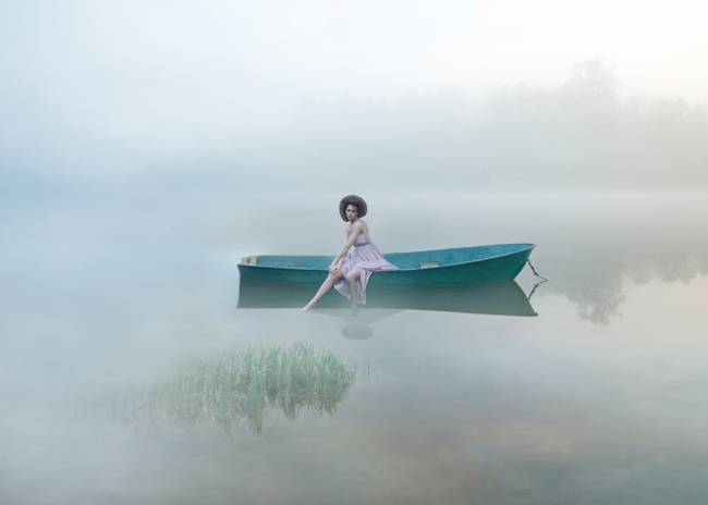 conceptual photography fine art of woman sitting in boat in foggy ice water