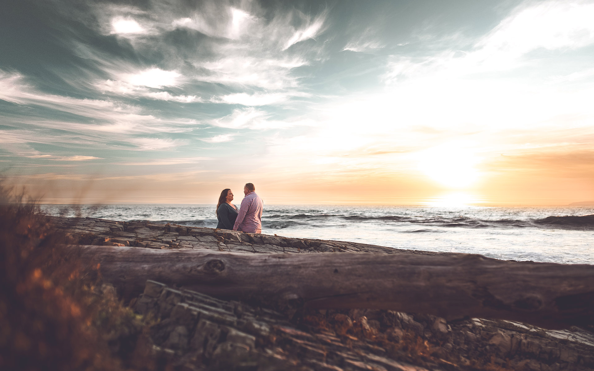 couple standing at beach sunset during engagement