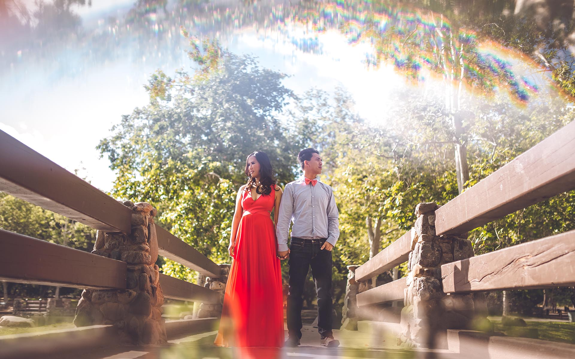 couple standing at bridge engagement session in orange county irvine park