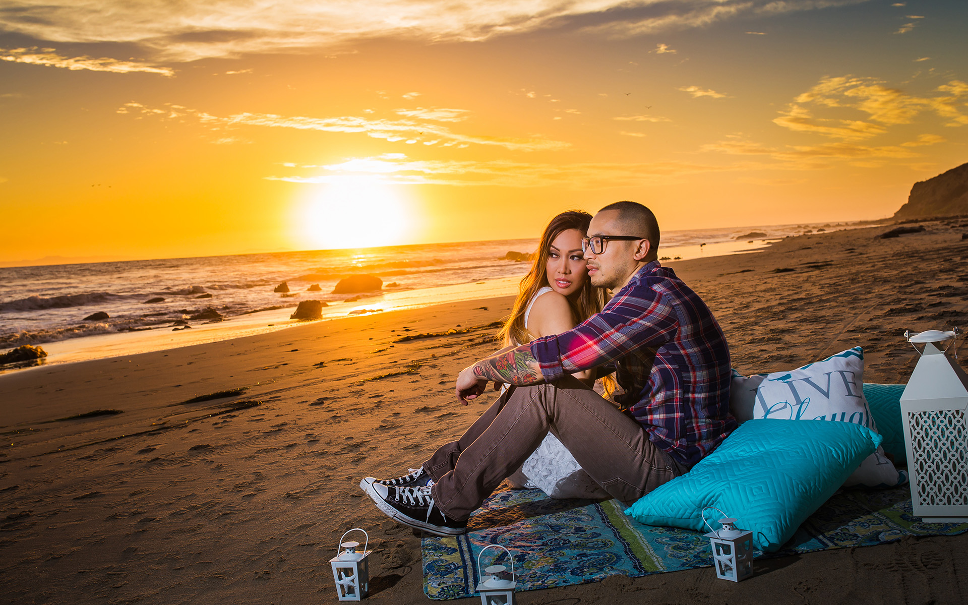 man and woman sitting at beach sunset engagement photography